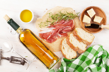 Prosciutto, wine, olives, parmesan and olive oil on wooden table. Top view Stock Photo