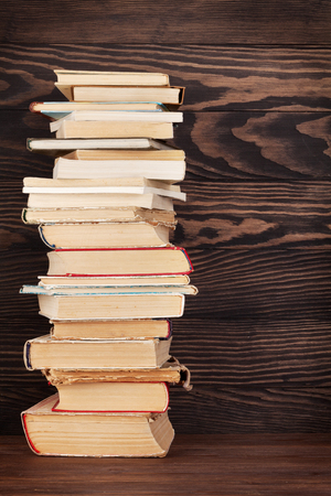 Stack of old books in front of wooden wall. School background. Education backdrop