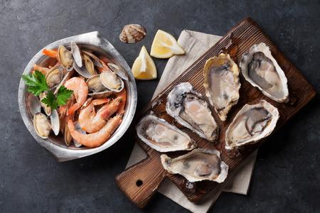 Verse zeevruchten op stenen tafel. Sint-jakobsschelpen, oesters en garnalen. Bovenaanzicht