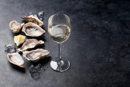 Huîtres ouvertes, glace et citron avec du vin blanc sur la table en pierre. Une demi-douzaine. Avec un espace de copie