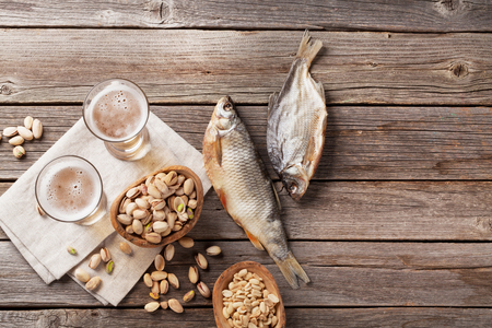 Lager beer and snacks on wooden table. Various nuts, salted fish. Top view with copy space