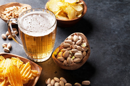 Lager beer and snacks on stone table. Nuts, chips. With copyspace Stock Photo
