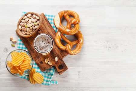 Lager beer and snacks on wooden table. Nuts, chips, pretzel. Top view with copy space Foto de archivo