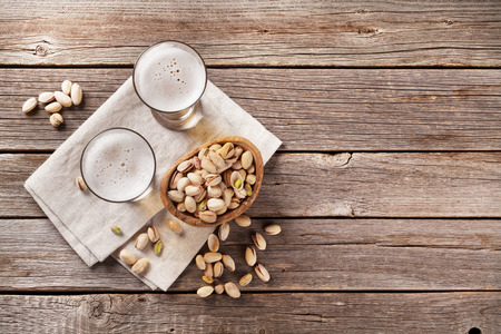 pistachio: Lager beer mug and snacks on wooden table. Top view with copy space Stock Photo