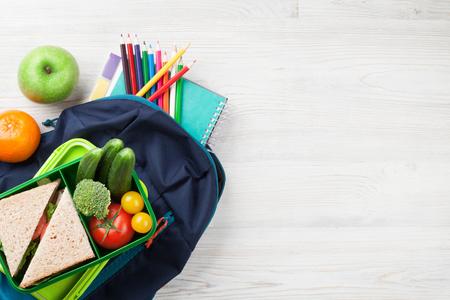 Brotdose mit Gemüse und Sandwich auf Holztisch. Kinder nehmen Lebensmittelbox und Schulrucksack mit. Draufsicht mit Textfreiraum