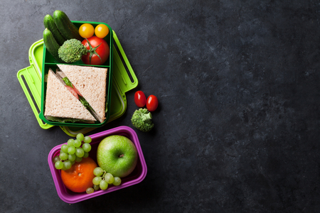 Lunch box with vegetables and sandwich. Kids take away food box and fruits. Top view on blackboard with space for your text