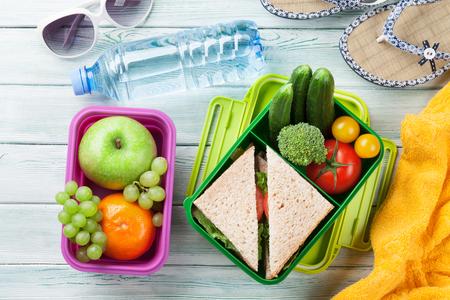 野菜と木の背景にサンドイッチのお弁当。フード ボックス、タオル、眼鏡ビーチを奪います。トップ ビュー 写真素材