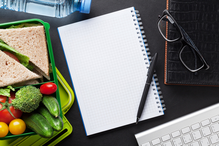 todo list: Office desk with supplies and lunch box with vegetables and sandwich. Top view with notepad for your text