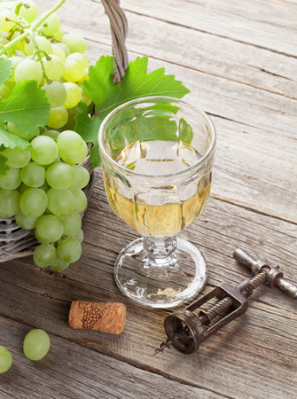 White grape in basket and glass of wine on wooden table