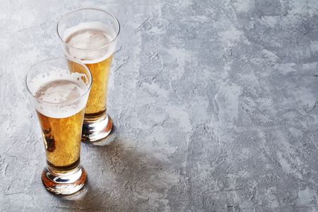 Lager beer glasses on stone table. With copy space