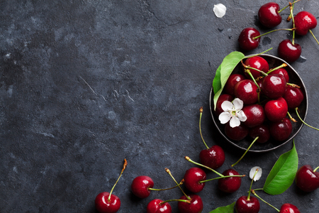 Fresh garden cherry in bowl on stone table. Top view with copy space