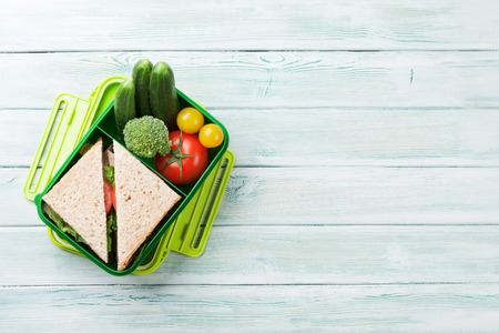 Lunch box with vegetables and sandwich on wooden background. Top view with space for your text Stock Photo