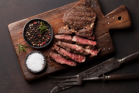 Grilled beef steak with spices on cutting board. Top view Zdjęcie Seryjne
