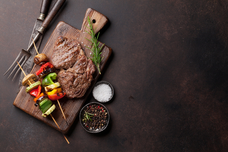Beef steak and grilled vegetables on cutting board on stone table. Top view with copy space