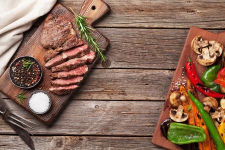 牛ステーキと木製のテーブルにまな板の上の野菜のグリル。コピー スペース平面図