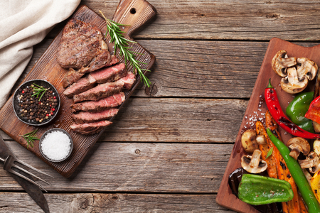 Beef steak and grilled vegetables on cutting board on wooden table. Top view with copy space Foto de archivo