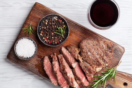 Grilled beef steak with spices on cutting board and red wine. Top view