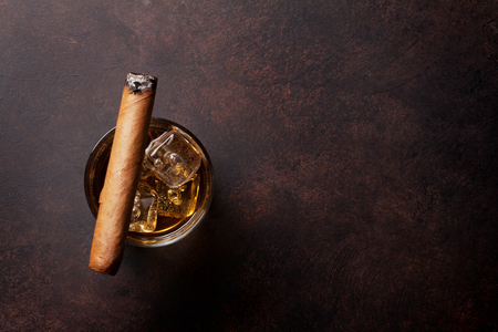Whiskey with ice and cigar. Top view with copy space