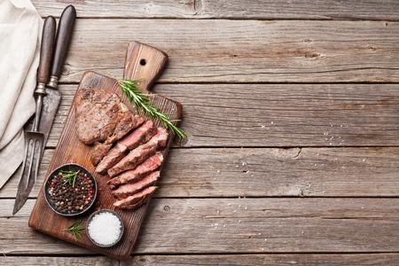 まな板の上のスパイス焼き牛ステーキ。コピー スペース平面図