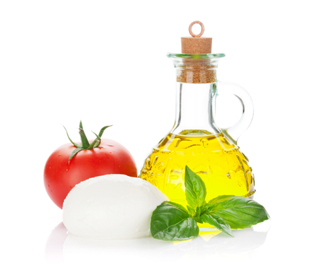 Mozzarella cheese, olive oil, tomato and basil herb leaves. Isolated on white background