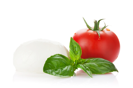 Mozzarella cheese, tomato and basil herb leaves. Isolated on white background Stock Photo