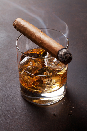 Whiskey with ice and cigar on dark stone table