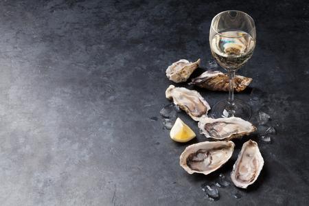 Geopende oesters, ijs en citroen en witte wijn op stenen tafel. Met kopie ruimte