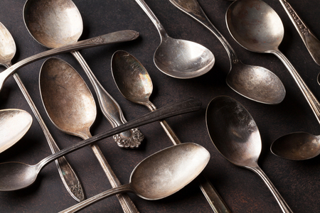 grunge silverware: Old vintage spoons on stone table.Top view