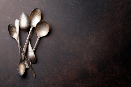 Old vintage spoons on stone table.Top view with copy space