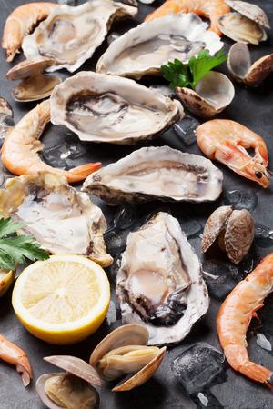Verse zeevruchten op stenen tafel. Oesters, garnalen en sint-jakobsschelpen. Bovenaanzicht