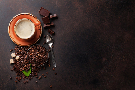 Coffee cup, beans, chocolate on stone background. Top view with copy space for your text Stok Fotoğraf