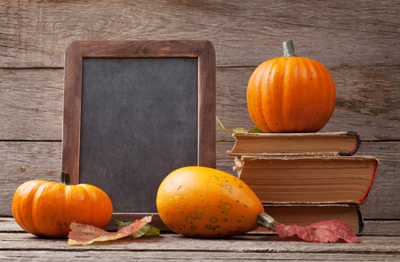 Autumn pumpkins on wooden table. View with chalkboard for copy space Stock Photo