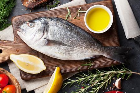 생선 요리와 재료. 황새, 레몬, 허브 및 향신료. 석재 테이블 위를 본다.