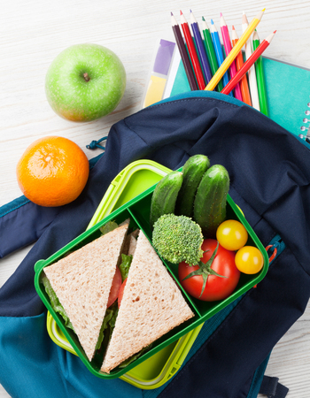 Lunch box with vegetables and sandwich on wooden table. Kids take away food box and school supplies. Top view Stock Photo