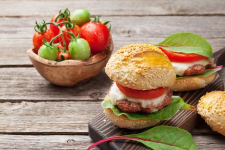 Zelfgemaakte hamburgers met rundvlees, kaas, tomaten, komkommer en salade op snijplank