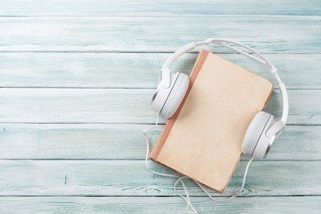 Audio book concept. Headphones and old book over wooden table. Top view with space for your text 版權商用圖片
