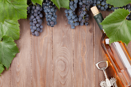 Red grape, wine bottle and corkscrew on wooden table. Top view with copy space Stock Photo