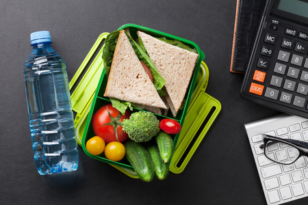 Office desk with supplies and lunch box with vegetables and sandwich. Top view Stockfoto