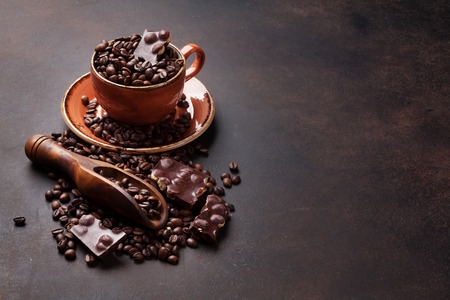 Coffee cup with roasted beans and chocolate on stone background. With copy space for your text Stok Fotoğraf