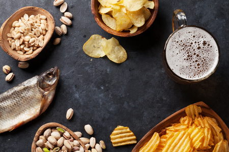 Lager beer mug and snacks on stone table. Nuts, chips, dry fish. Top view with copy space Stock Photo