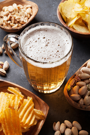 Lager beer mug and snacks on stone table. Nuts, chips Imagens