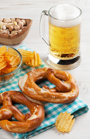 Lager beer and snacks on wooden table. Nuts, chips, pretzel Stock Photo
