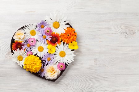 Garden flowers in heart shaped gift box on wooden background. Top view with copy space