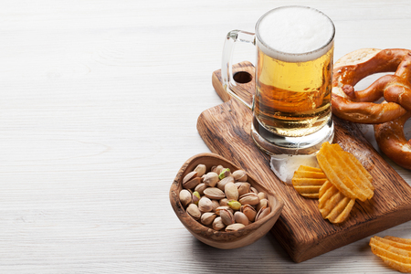 Lager beer and snacks on wooden table. Nuts, chips, pretzel. With copy space Stock Photo