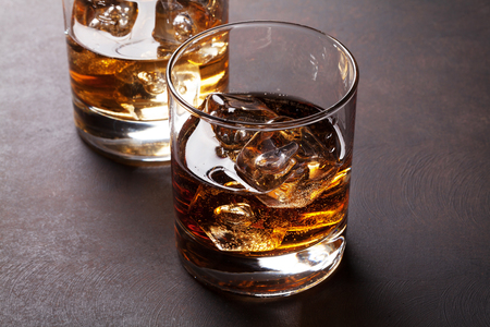 Whiskey with ice on stone table 写真素材
