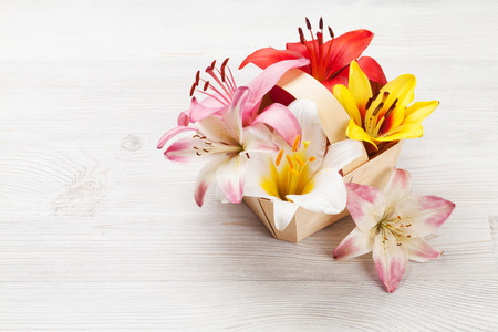 Colorful lily flowers basket on wooden background with space for your greetings Zdjęcie Seryjne