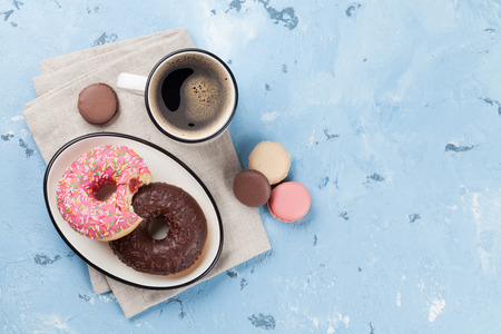 Coffee cup and colorful donuts on stone table. Top view with copy space