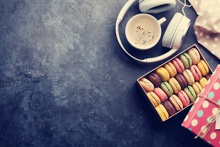 Colorful macaroons in a gift box and headphones on stone table. Sweet macarons. Top view with copy space for your text. Toned Stock Photo
