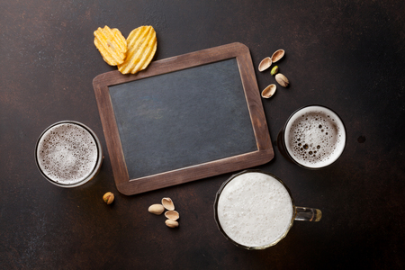 Lager beer and snacks on stone table. Nuts, chips. Top view with chalkboard for copy space