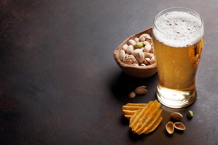 Pils en snacks op stenen tafel. Noten, chips. Met kopie ruimte